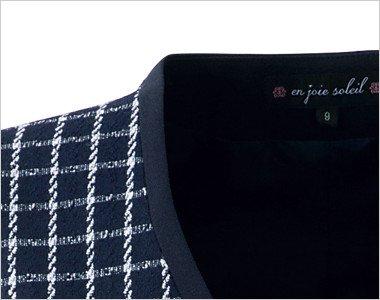 チェック柄を引き締める黒パイピングの襟元